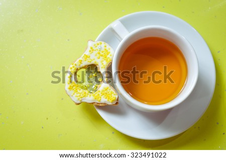 Close up picture of ginger cookie and cup of tea on green background copy space - stock photo