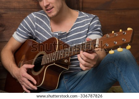 Close-up picture of man playing the guitar. Young man in jeans and stripped T-shirt playing his favourite songs.