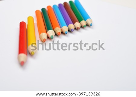 Close up picture of many little colored pencil crayons on white background. Assortment of sharpened colored pencils/ Colored drawing pencils. Selective focus. Copy space - stock photo