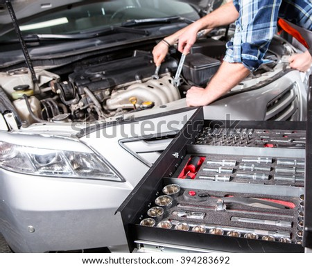 Close-up picture of mechanical workshop tools. Professional car mechanic using different tools for working in auto repair service. - stock photo
