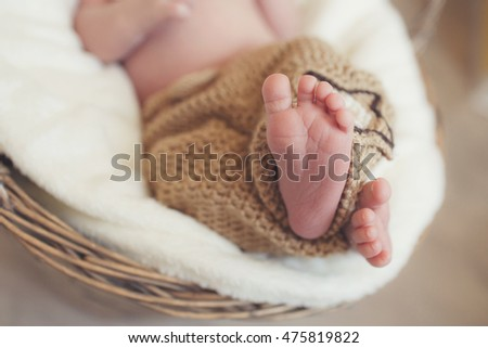 Close up picture of new born baby feet in knitted plaid. Little fingers. Newborn baby's legs. A closeup to babies feet