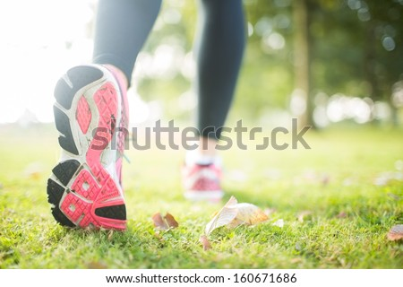 Close up picture of pink sole from running shoe in a park on a sunny day - stock photo
