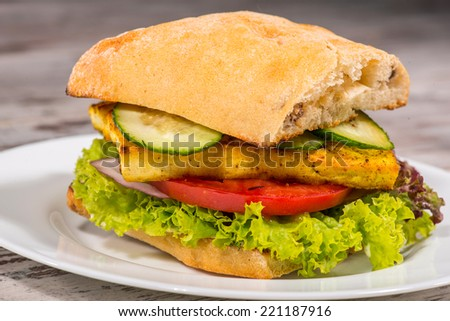 Close-up picture of tasty vegetarian sandwich with tofu, tomatoes, salad and cucumber on the white plate standing on the wooden table in vegan caffee - stock photo