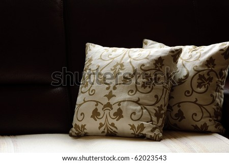 close up picture of two pillows on a leather sofa - stock photo