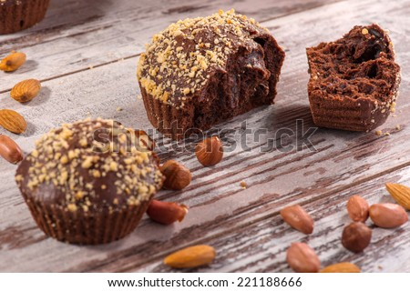 Close-up picture of two tasty chocolate cupcakes decorated with almonds and hazelnut on wooden table in cafe, with selective focus only on one broken cupcake, with copy place - stock photo