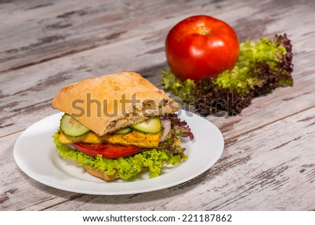 Close-up picture of vegetarian sandwich with tofu, tomatoes, salad and cucumber on the white plate on the wooden table in vegan caffee, with one tomato and salad standing near a plate, with copy place - stock photo
