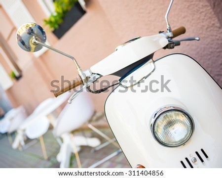 Close-up picture of vintage white scooter, outdoors. - stock photo