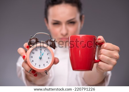 Close-up picture with selective focus alarm clock and a red cup in hands of young woman isolated on grey background concept of time management and coffee-break - stock photo