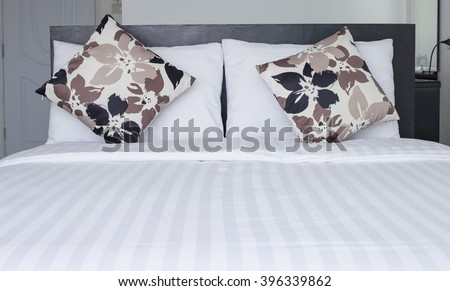 Close up pillow on white bedding sheets - stock photo