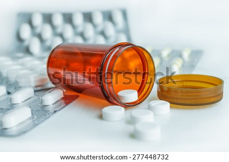 close up pills in pill bottle with blister pack medicine background - stock photo