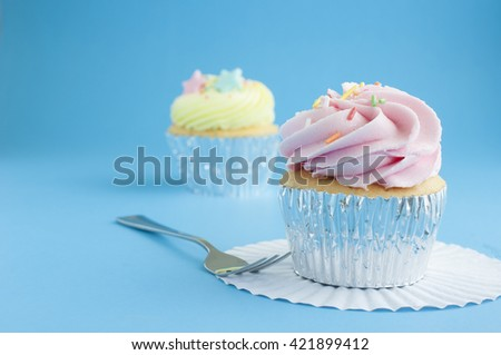Close up pink cup cake with icing on blue background - stock photo