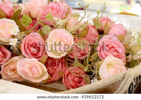 Close up pink roses with petal in the basket on the wooden background - stock photo