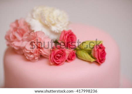Close-up pink wedding cake with roses against  copy space background - stock photo