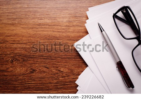 Close up Plain and with Pen and Glasses on Top of Brown Wooden Table with Copy Space on Left Side. - stock photo