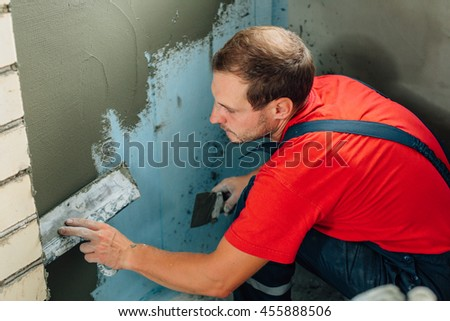 close up plasterer concrete worker at wall