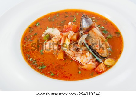 Close up Plate of Delicious Italian soup with seafood and vegetables decorated with herbs and shell mussel isolated on the white background - stock photo