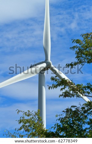 close up pof wind generator's propellers tree in the forground - stock photo