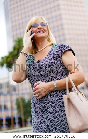 Close Up portrait happy smiling attractive business woman in glasses 60 years in the downtown talking with mobile phone, Lifestyle woman on phone, Business concept woman calling on the phone in street - stock photo