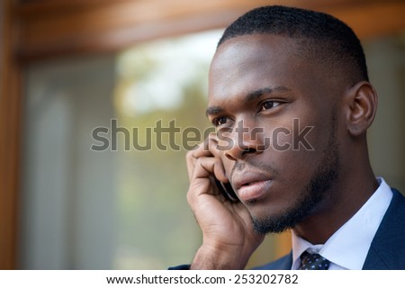 Close up portrait of a african american businessman talking on cell phone - stock photo