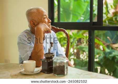 close-up portrait of a asian senior man thinking about something - stock photo