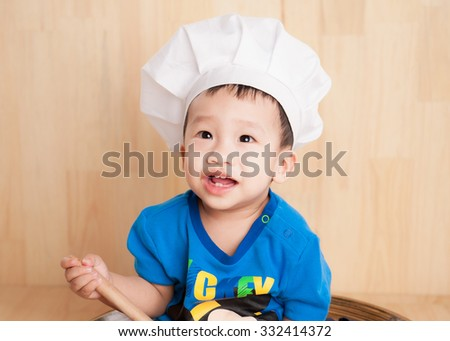 Close up portrait of a baby sitting wearing a chef hat - stock photo