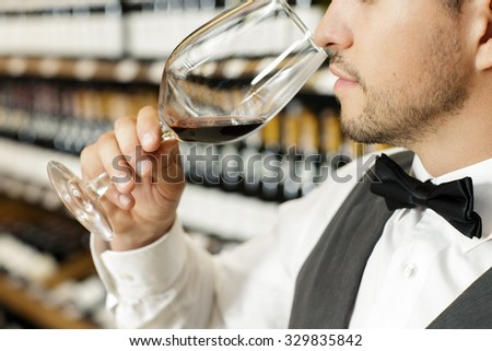 Close up portrait of a bearded sommelier smelling red wine from the large glass in a wine store, wine shelves on the background
