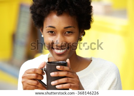 Close up portrait of a beautiful african american woman smiling with cup of a coffee - stock photo