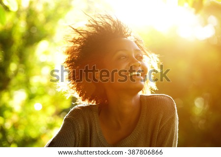 Close up portrait of a beautiful african american woman smiling with sunset - stock photo