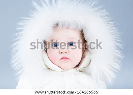 Close up portrait of a beautiful baby in a white winter jacket - stock photo