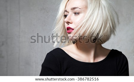 Close-up portrait of a beautiful blonde with red lips on a gray background - stock photo