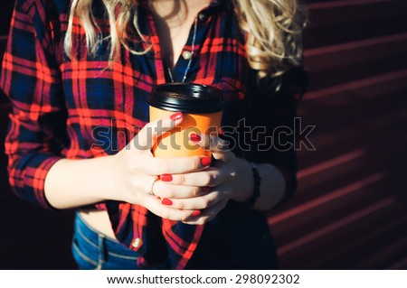 close-up portrait of a beautiful bright girl young sexy  blonde with red lips with curly hair with a cup of coffee  to go in a plaid shirt and denim shorts smiling and posing - stock photo