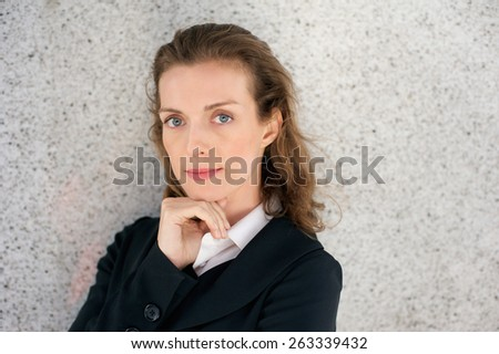 Close up portrait of a beautiful business woman posing with hand on chin - stock photo