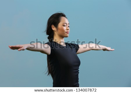 Close up portrait of a beautiful Chinese woman standing meditating in a yoga pose. Asian Woman in black t-shirt Performing yoga. - stock photo