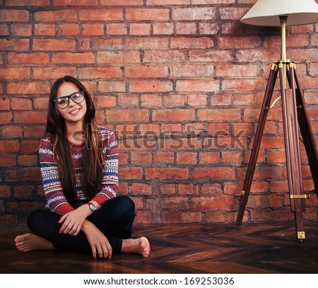 Close up portrait of a beautiful cute teen girl sitting on the floor - stock photo