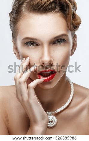 Close-up portrait of a beautiful girl with a necklace, a hand touched his lips. Wedding hair and makeup. Beauty Girl. - stock photo