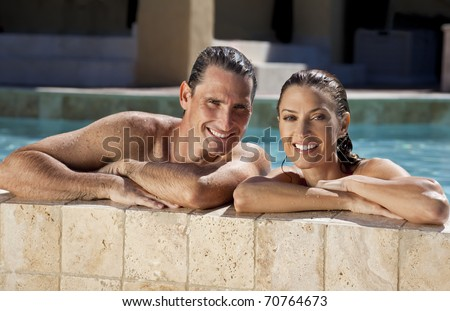 Close up portrait of a beautiful happy man and woman couple resting on their hands at the side of a sun bathed swimming pool smiling with perfect teeth. - stock photo