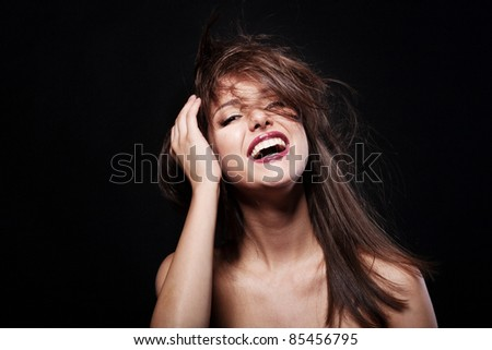 Close-up portrait of a beautiful laughing brunette model in studio on black background