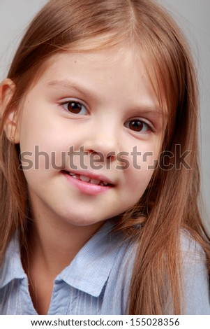 Close-up portrait of a beautiful little girl with long brown hair on gray background on Beauty and Fashion