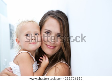 Close up portrait of a beautiful mother holding baby - stock photo