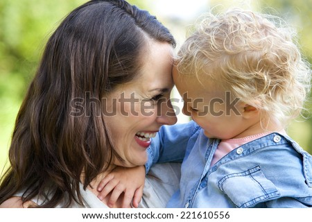 Close up portrait of a beautiful mother laughing with baby  - stock photo