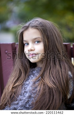 Close up portrait of a beautiful nine year old little girl in autumn park - stock photo