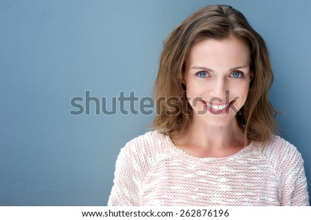 Close up portrait of a beautiful older woman smiling with sweater on blue background  - stock photo