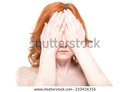 Close-up portrait of a beautiful redhead woman, covering her eyes. Isolated on white background. Facial expression and emotions.