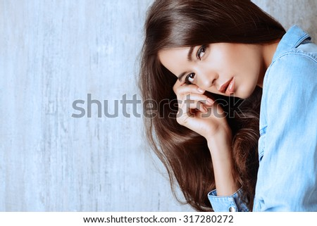Close-up portrait of a beautiful sensual woman in jeans clothes. Copy space. Fashion. - stock photo