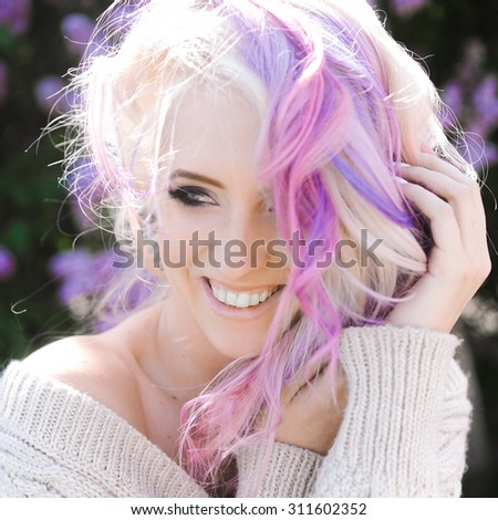 close-up portrait of a beautiful sexy young blonde girl hipster with lilac and pink hair  posing  - stock photo