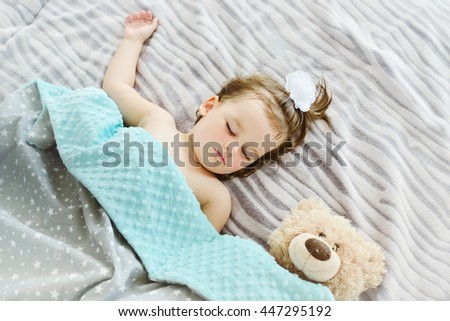 Close-up portrait of a beautiful sleeping baby girl. Cute infant kid with teddy bear. Child portrait in pastel tones.Top view image. - stock photo