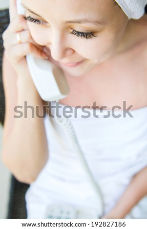 Close up portrait of a beautiful smile young woman in towel with phone in hand - stock photo
