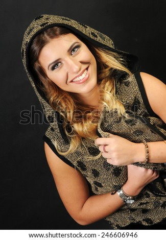 close up portrait of a beautiful smiling caucasian girl with long curly hair wearing Golden vest with black polka dots holding her hands crossed behind her chest - stock photo