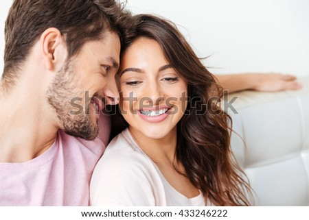 Close-up portrait of a beautiful smiling couple sitting on the couch isolated on white background - stock photo