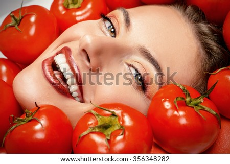 Close-up portrait of a beautiful smiling woman among the tomato. Healthy eating concept. Make-up, cosmetics. - stock photo